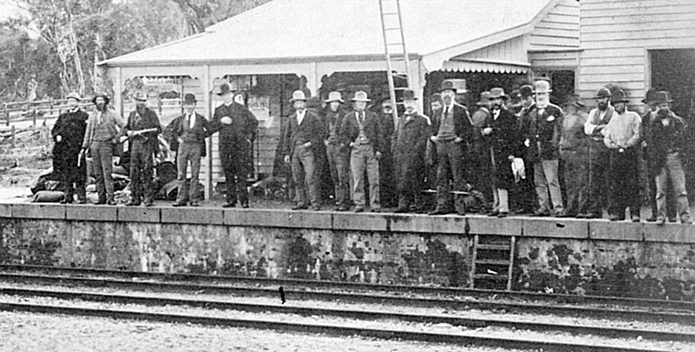 Spectators and plainclothed police pose on the railway platform in the late stages of the siege. Fifth from the left is Father Gibney. Note the group at right with their backs to the camera as they crowd around the door of the office where Ned Kelly lay. Imagine: La Trobe Collection, State Library of Victoria
